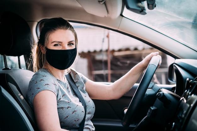 Młoda kobieta w czarnej masce medycznej siedzi w samochodzie z kierownicą po lewej stronie