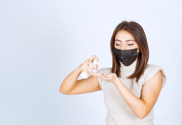 Młoda kobieta w czarnej masce medycznej za pomocą sprayu