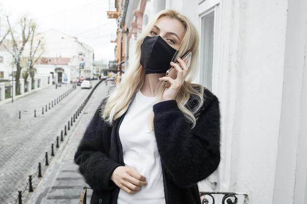 Młoda kobieta w czarnej masce stoi na balkonie biura i pisze przez telefon