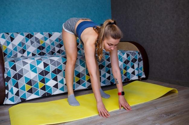 Młoda kobieta w czarnej odzieży sportowej ćwiczy jogę, stojąc w pozie zgięcia z przodu, wykonując ćwiczenie, wysportowana dziewczyna ćwicząca w domu lub w studio jogi z szarymi ścianami, rozciąganie ciała
