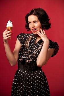 Młoda kobieta w czarnej rocznik sukni stoi łasowania lody nad czerwienią