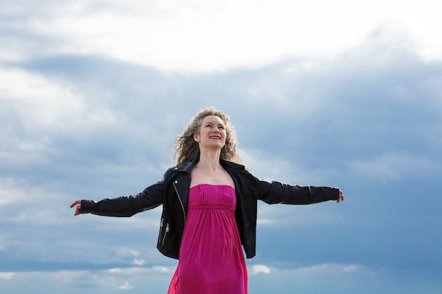 Młoda kobieta w czarnej skórzanej kurtce i różowej sukience rozłożyła ręce na boki