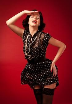 Młoda kobieta w czarnej sukience vintage stojących na czerwono