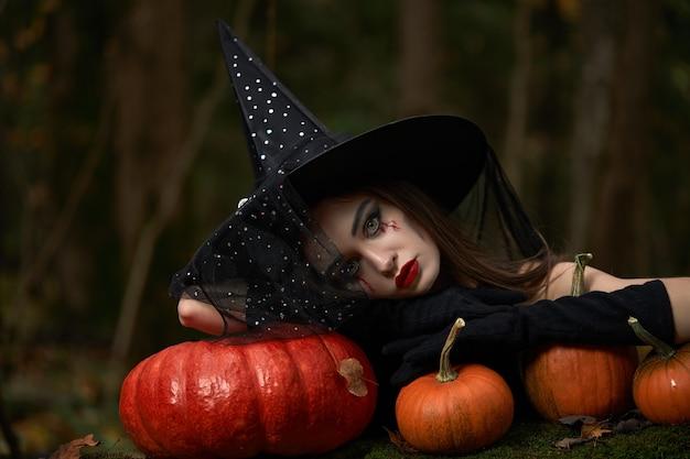 Młoda kobieta w czarnej sukience z kapeluszem czarownicy i pomarańczową dynią umieszczonej w lesie, koncepcja halloween. motyw horroru.