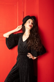 Młoda kobieta w czarnej sukni i kapeluszu stoi