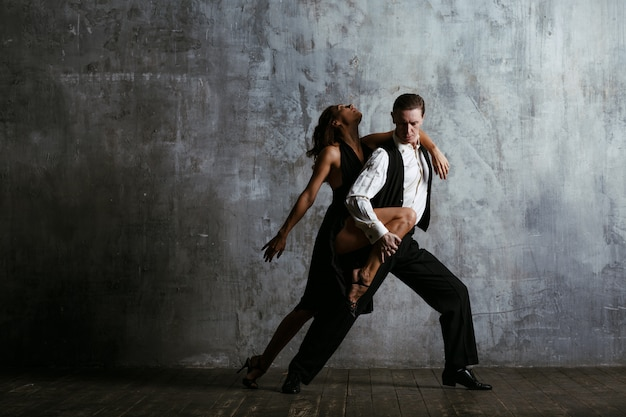 Młoda kobieta w czarnej sukni i mężczyzna tańczy tango