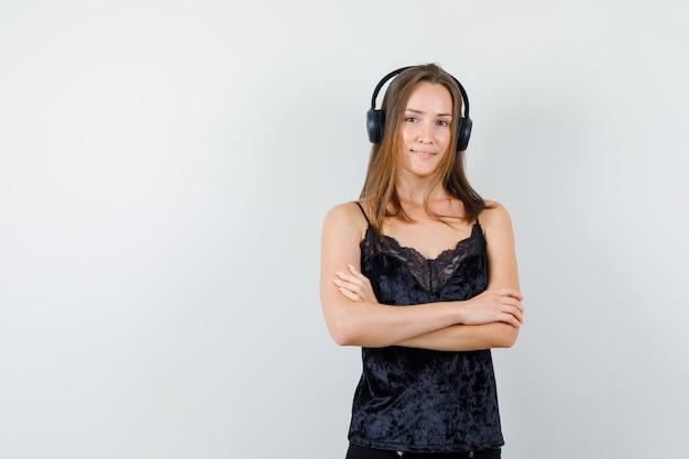 Młoda kobieta w czarny podkoszulek stojący ze słuchawkami i patrząc optymistycznie