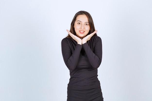 Młoda kobieta w czarnych ubraniach, dając piękne pozy