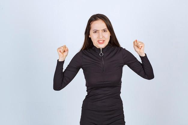 Młoda kobieta w czarnych ubraniach jest zaskoczona i podekscytowana
