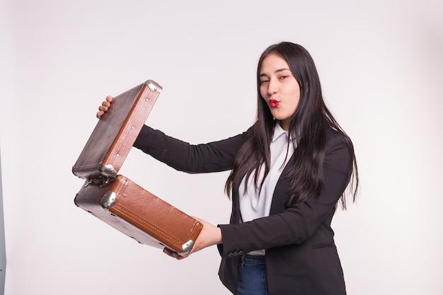 Młoda kobieta w czarnym garniturze otworzyć walizkę retro na białym tle