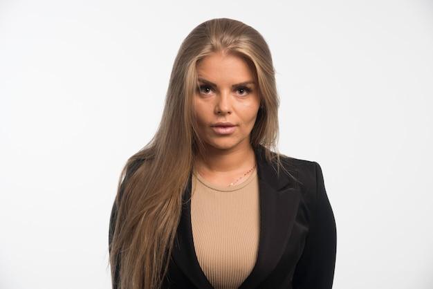 Młoda kobieta w czarnym garniturze pozowanie.