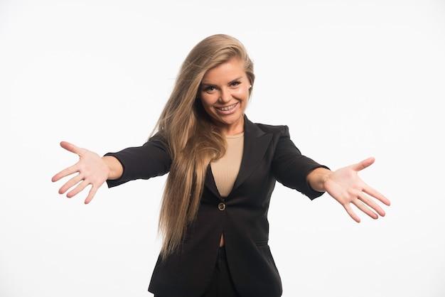 Młoda kobieta w czarnym garniturze sprawia, że prezentacja gestami ręki.