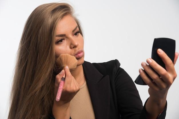 Młoda kobieta w czarnym garniturze stosowania makijażu na policzku.