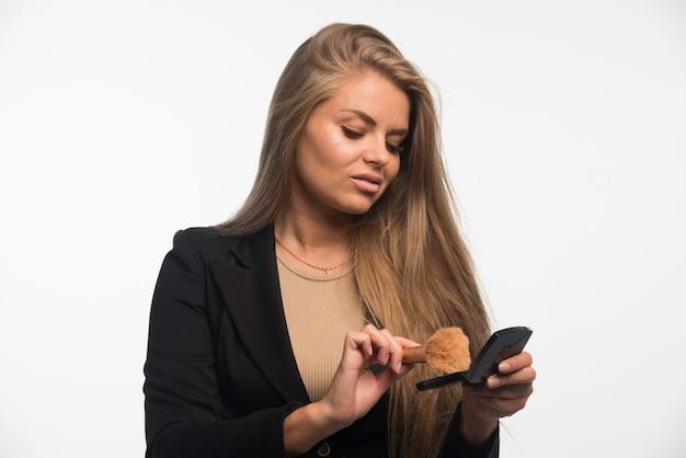 Młoda kobieta w czarnym garniturze stosowania makijażu pędzlem.