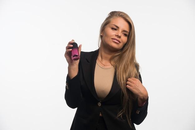 Młoda kobieta w czarnym garniturze stosuje perfumy.