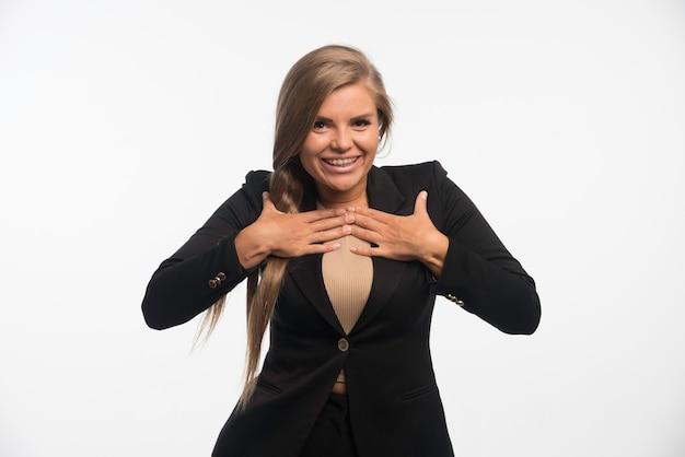 Młoda kobieta w czarnym garniturze wygląda na szczęśliwą i wskazuje się.