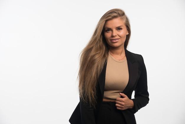 Młoda kobieta w czarnym garniturze wygląda pewnie i profesjonalnie.
