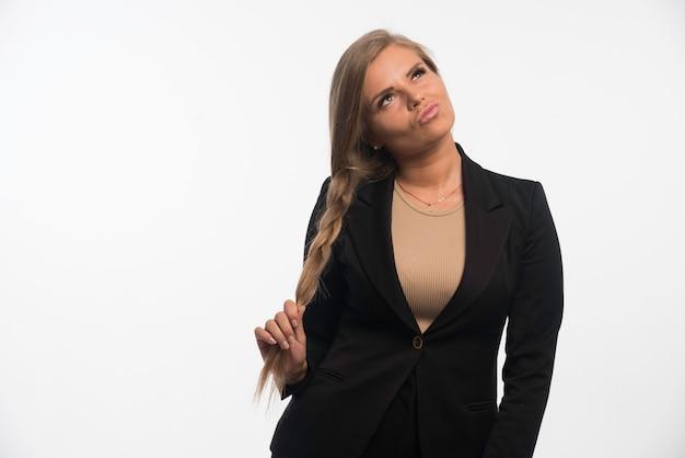 Młoda kobieta w czarnym garniturze wygląda pewnie.