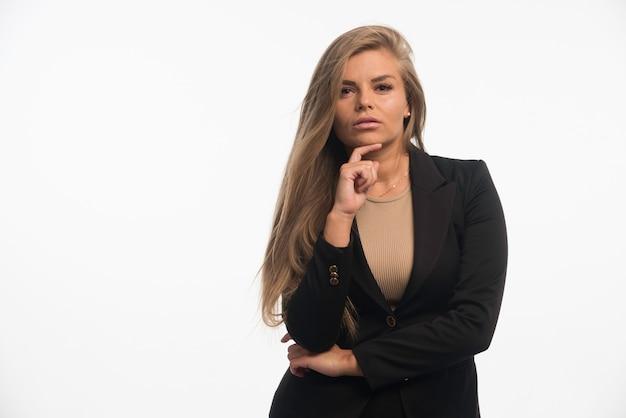 Młoda kobieta w czarnym garniturze wygląda uwodzicielsko.