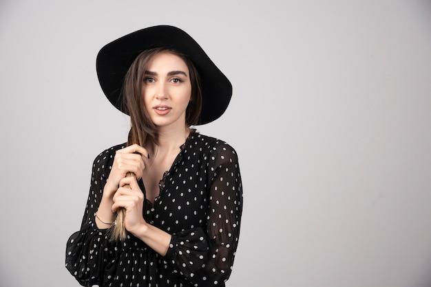 Młoda kobieta w czarnym kapeluszu bawi się jej włosami.
