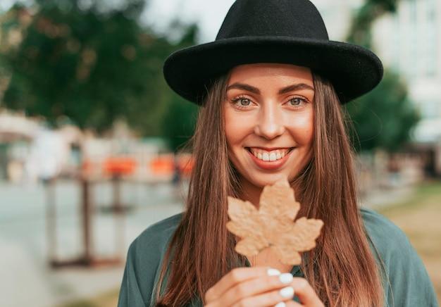 Młoda kobieta w czarnym kapeluszu, trzymając liść