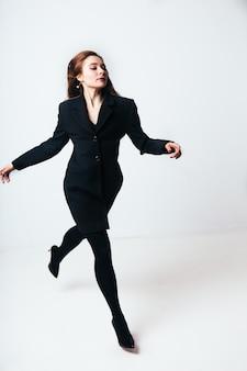 Młoda kobieta w czarnym kostiumu doskakiwaniu na białym tle. dziewczyna w czerni na białym tle