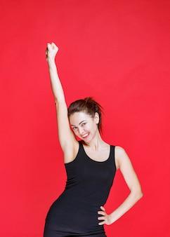 Młoda kobieta w czarnym podkoszulku stojąca na czerwonej ścianie i demonstrująca mięśnie ramion