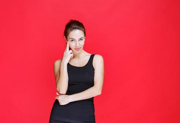 Młoda kobieta w czarnym podkoszulku stojąca na czerwonej ścianie i myśląca