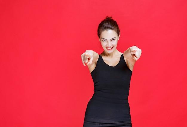 Młoda kobieta w czarnym podkoszulku stojąca na czerwonej ścianie i pokazująca osobę z przodu