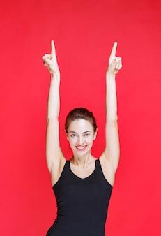 Młoda kobieta w czarnym podkoszulku stojąca na czerwonej ścianie i wskazująca w górę
