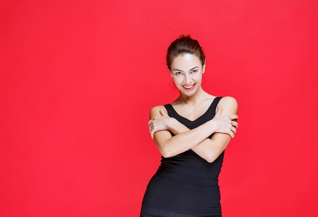 Młoda kobieta w czarnym podkoszulku stojąca na czerwonej ścianie
