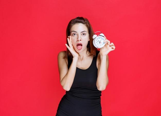Młoda kobieta w czarnym podkoszulku trzyma budzik i wygląda na przerażoną i zdziwioną