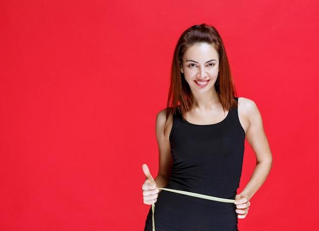 Młoda kobieta w czarnym podkoszulku trzyma miarkę, mierzy jej talię i czuje się dobrze