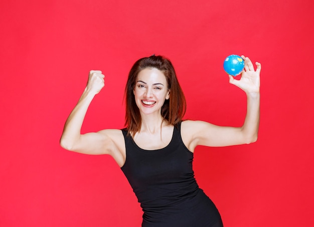 Młoda kobieta w czarnym podkoszulku trzyma mini-światową kulę ziemską i czuje się silna