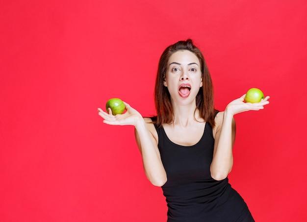 Młoda kobieta w czarnym podkoszulku trzyma zielone jabłka i wygląda na zaskoczoną