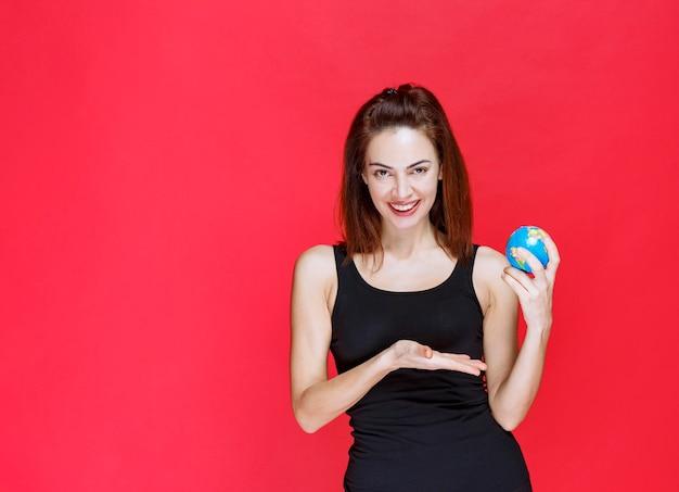 Młoda kobieta w czarnym podkoszulku trzymająca mini kulę ziemską