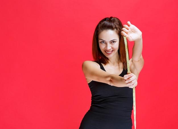 Młoda kobieta w czarnym podkoszulku trzymająca taśmę mierniczą