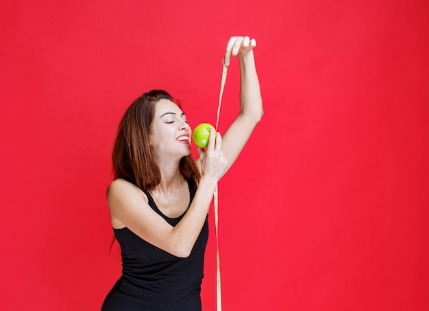 Młoda kobieta w czarnym podkoszulku trzymająca zielone jabłka i miarkę
