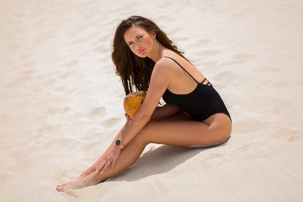 Młoda kobieta w czarnym stroju kąpielowym z kokosowym koktajlem na plaży