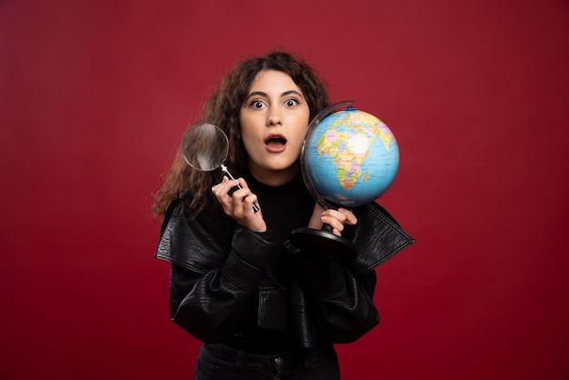 Młoda kobieta w czarnym stroju trzyma kulę ziemską z lupą.