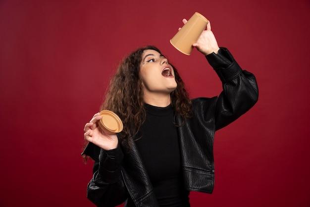 Młoda kobieta w czarnym stroju z otwartą pustą filiżanką.