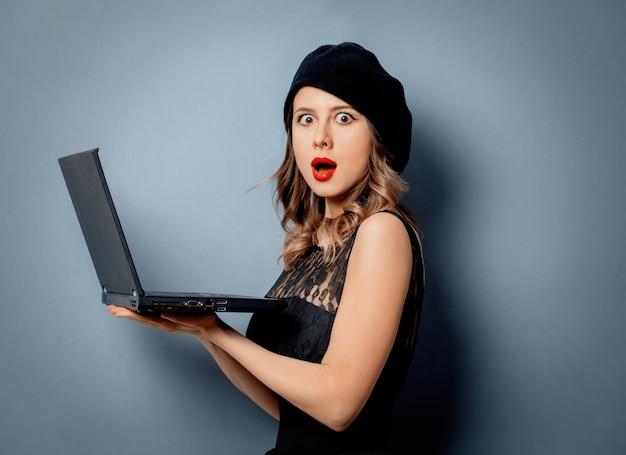 Młoda kobieta w czerni sukni z notatnikiem na szarości ścianie