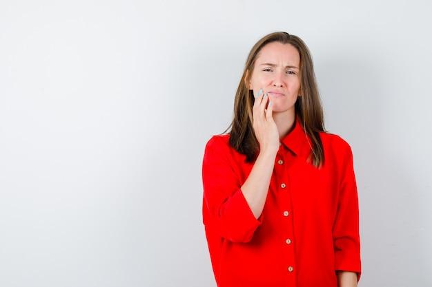 Młoda kobieta w czerwonej bluzce cierpi na ból zęba i wygląda na bolesną, widok z przodu.