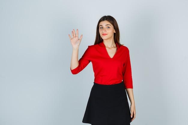 Młoda kobieta w czerwonej bluzce, czarnej spódnicy macha ręką na powitanie i wygląda uroczo