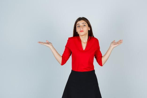 Młoda kobieta w czerwonej bluzce, czarnej spódnicy pokazuje bezradny gest i wygląda na zdziwioną