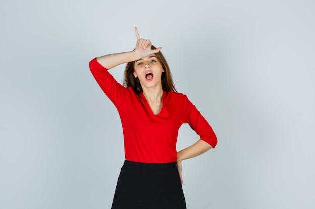 Młoda kobieta w czerwonej bluzce, czarnej spódnicy pokazuje gest przegrany