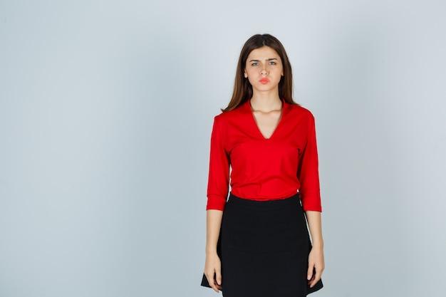 Młoda kobieta w czerwonej bluzce, czarnej spódnicy stojącej prosto