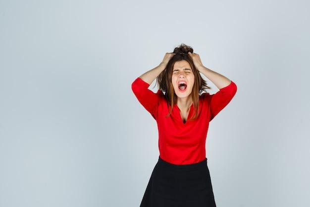 Młoda kobieta w czerwonej bluzce, czarnej spódnicy, trzymając ręce na głowie, trzymając usta otwarte