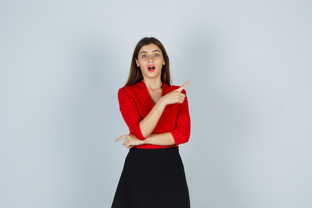 Młoda kobieta w czerwonej bluzce, czarnej spódnicy, wskazując w prawo z palcem wskazującym