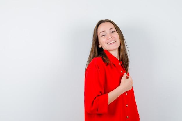 Młoda kobieta w czerwonej bluzce pozuje, stoi bokiem i wygląda na zadowoloną.
